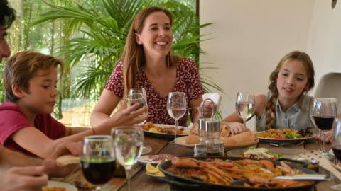 vídeos y material grabado en eventos de stock de familia multigeneracional disfrutando de la conversación al mediodía de la comida - cuatro personas
