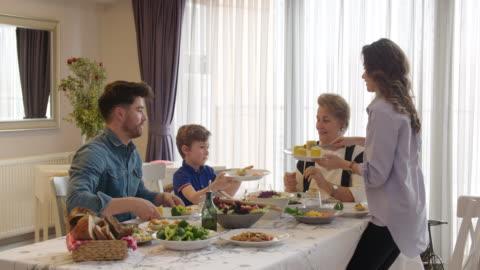 vídeos y material grabado en eventos de stock de familia multigeneracional que tiene una cena vegana - mesa de comedor