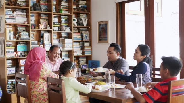 multi-generation family having food at table - bookshelf stock videos & royalty-free footage
