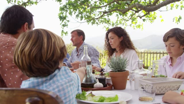 vídeos y material grabado en eventos de stock de familia de múltiples generaciones almorzando en la mesa - comida del mediodía