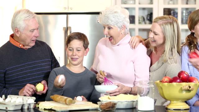Multi-generation family in kitchen making an apple pie