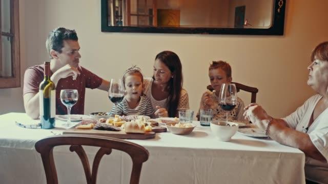 picada テーブルの後ろでワインを飲んでいる多世代の家族 (スローモーション) - 広角撮影点の映像素材/bロール