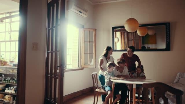 vidéos et rushes de famille multi-génération est fait des devoirs avec les enfants (ralenti) - famille multi générations