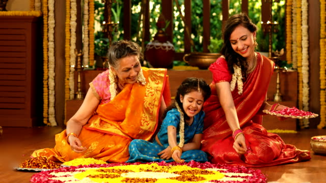 MS Multi-generation family making flower rangoli during pongal festival / New Delhi, India