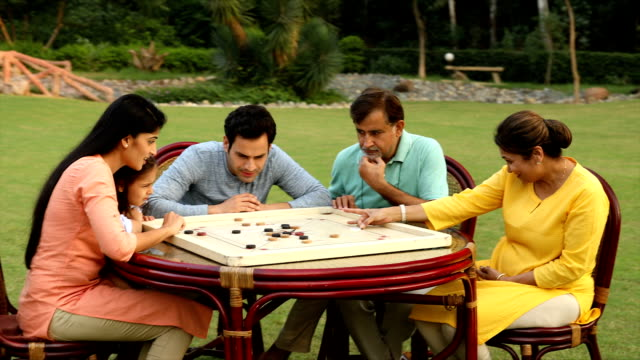 ms multi-generation family playing carrom board together in backyard / delhi, india - carrom stock videos & royalty-free footage