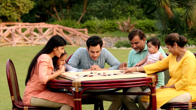 ms zi multi-generation family playing carrom board together in backyard / delhi, india - carrom stock videos & royalty-free footage