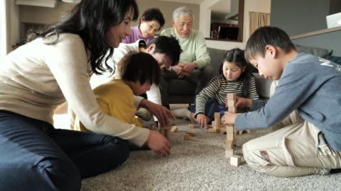 vídeos y material grabado en eventos de stock de familia de múltiples generaciones jugando en el bloque - vida sencilla