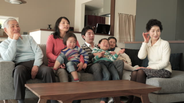 多世代家族でテレビをご覧のリビングルーム - リビング点の映像素材/bロール