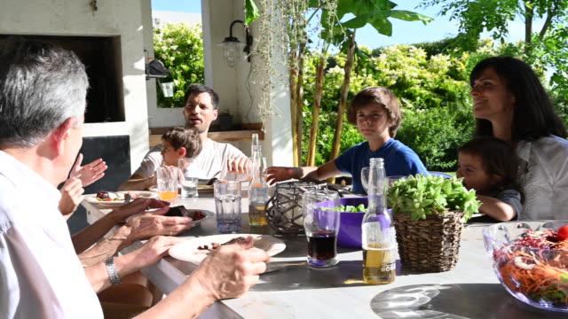 vídeos y material grabado en eventos de stock de familia hispana de varias generaciones comiendo comida al aire libre - 4 5 años