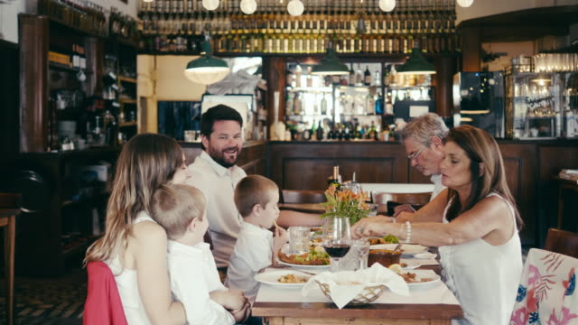 vídeos de stock e filmes b-roll de multi-generation latin-american family eating at the restaurant - latin american and hispanic ethnicity