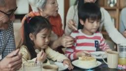Multi-generational Chinese family eating birthday cake