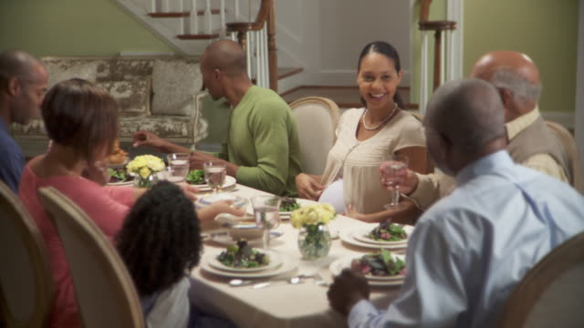 ms, pan, multigenerational family at table, senior woman bringing turkey, richmond, usa - continuity stock videos and b-roll footage