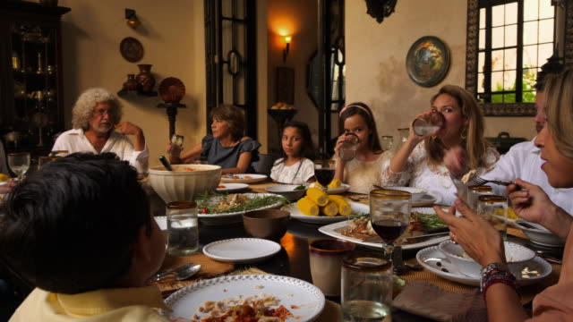 pan multigenerational family dining together during celebration dinner - tischflächen aufnahme stock-videos und b-roll-filmmaterial