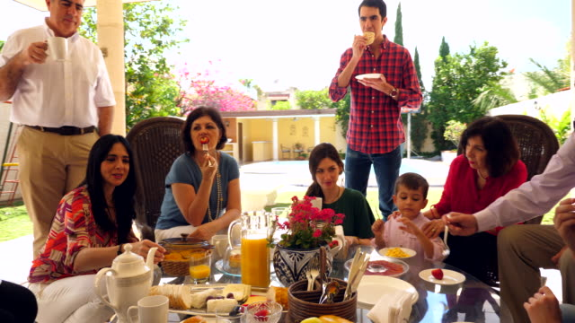 ws multigenerational family eating breakfast together during outdoor brunch - brunch stock videos & royalty-free footage