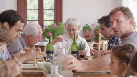 familj med flera generationer njuter av mat hemma - mellanstor grupp av människor bildbanksvideor och videomaterial från bakom kulisserna