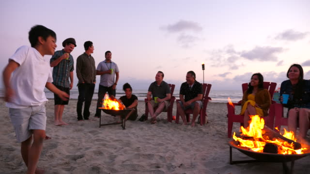 pan multigenerational family hanging out by fire during beach party - pacific islander family stock videos & royalty-free footage