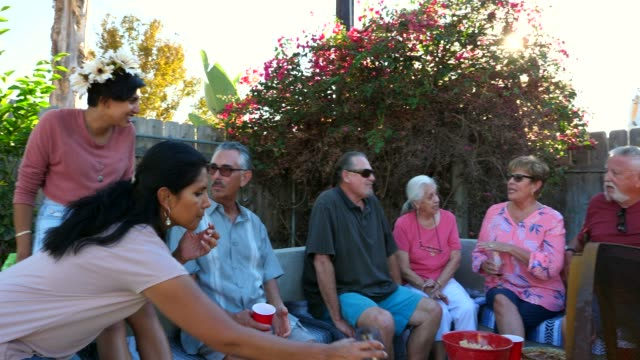 PAN Multigenerational family hanging out together during backyard barbecue
