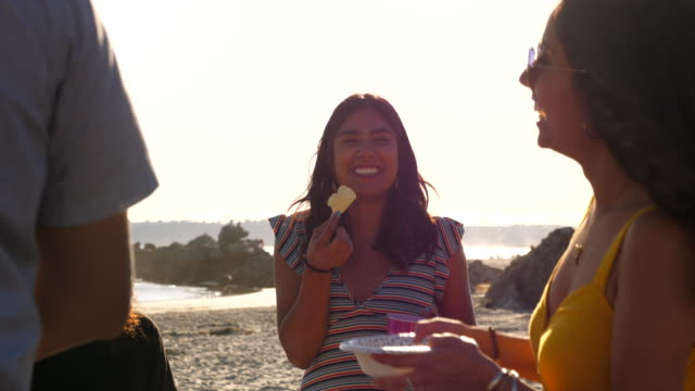 pan multigenerational family hanging out together during beach party on summer evening - pacific islanders stock videos & royalty-free footage