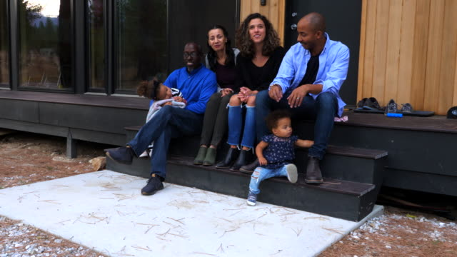 ms multigenerational family hanging out together on porch of modern cabin - front stoop stock videos & royalty-free footage