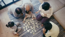 Multi-generational family playing Karuta card game on New Year's Eve