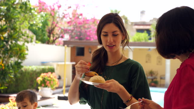 ms multigenerational family sharing brunch in backyard - brunch stock videos & royalty-free footage
