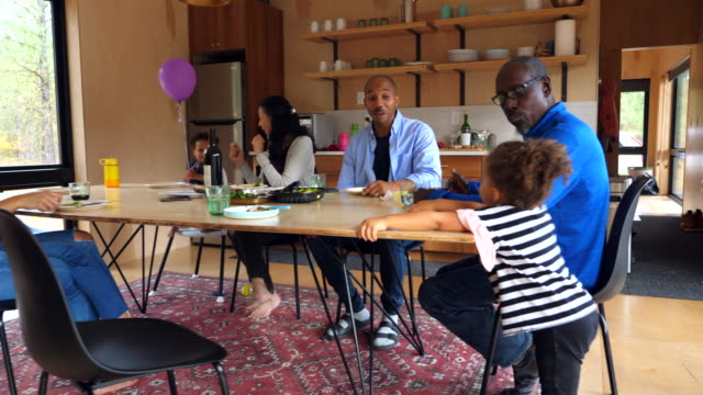 ms multigenerational family sharing dinner at table in modern cabin - tischflächen aufnahme stock-videos und b-roll-filmmaterial