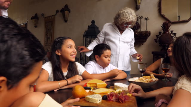 pan multigenerational family sharing food at table together during celebration - part of a series stock-videos und b-roll-filmmaterial