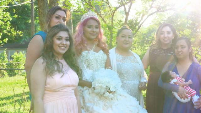 ms pan multigenerational female family members posing for quinceanera photos in backyard - 14 15 anni video stock e b–roll