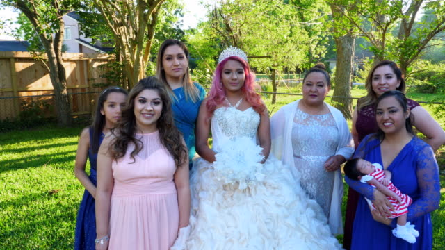ms zi zo multigenerational female family members posing for quinceanera photos in backyard - 14 15 anni video stock e b–roll