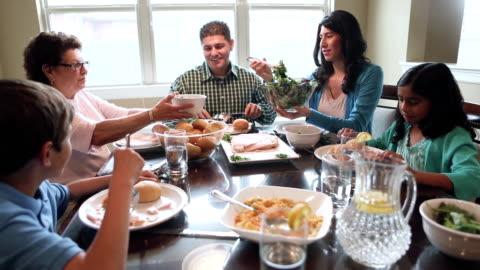 vídeos y material grabado en eventos de stock de multi-generacional hispano familia disfrutando de la cena y de tiempo de calidad para estar juntos - mesa de comedor