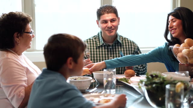 Multi-generational Hispanic family having dinner together at home