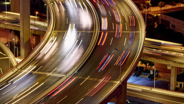 4k: multilevel viaduct traffic at night time lapse - bright colour stock videos and b-roll footage