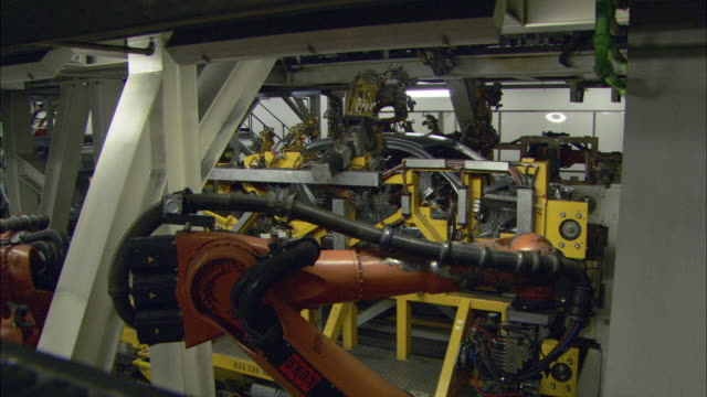 CU Multiple car assembly robots at work constructing car and placing car parts together in BMW car plant / Munich, Bavaria, Germany