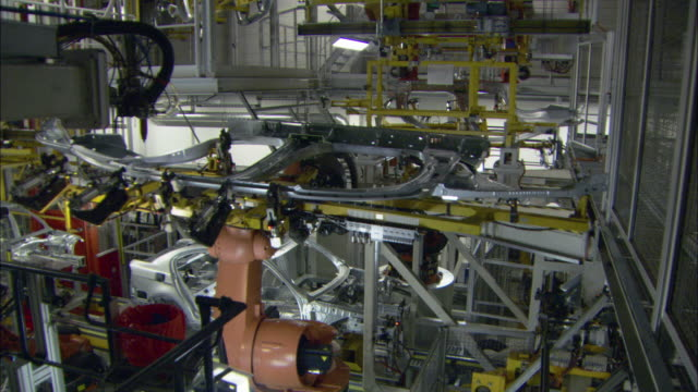 stockvideo's en b-roll-footage met ms multiple car assembly robots rotate and maneuver car parts into place while constructing single bmw vehicle in car plant / munich, bavaria, germany  - autofabriek