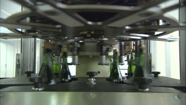 vidéos et rushes de cu multiple champagne bottles move quickly on conveyor belt through bottling machine throughout / reims, champagne, france - chaîne de production
