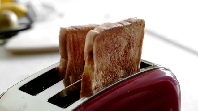 Multiple clips of toaster popping up toast
