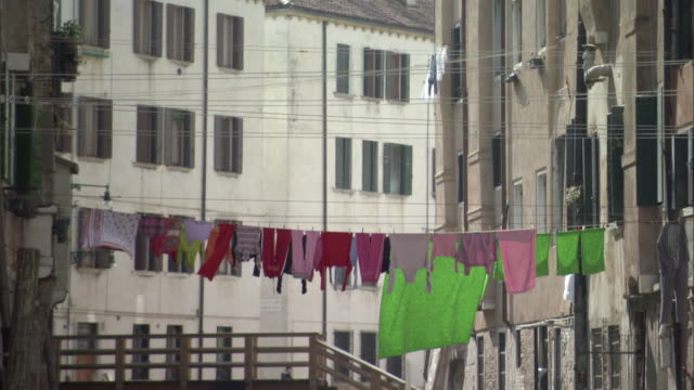 ms tu multiple clothes hanging from clothing lines attached to buildings / venice, veneto, italy - fare il bucato video stock e b–roll
