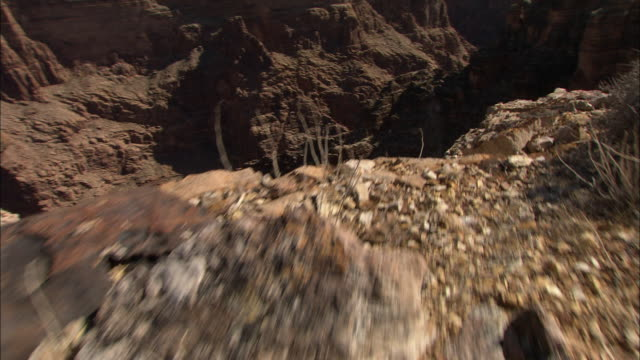 multiple crane push-in - rocky desert terrain plunges to a deep canyon crossed by fissures. / arizona, usa - tal stock-videos und b-roll-filmmaterial