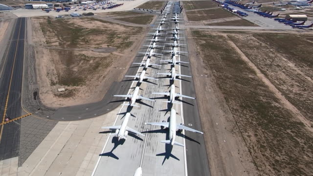 multiple delta jets parked on a runway at southern california logistics airport. they are being stored there due to decrease in airline activity due... - stationary stock videos & royalty-free footage