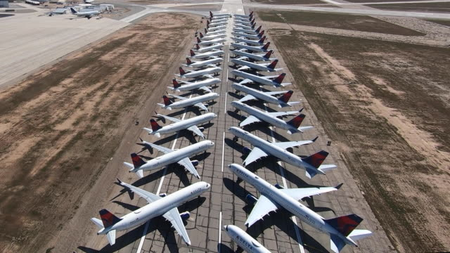 vidéos et rushes de multiple delta jets parked on a runway at southern california logistics airport. they are being stored there due to decrease in airline activity due... - stationary