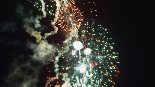 vídeos y material grabado en eventos de stock de multiple discharges of rockets explode in layered starbursts fading into sparks - sparks