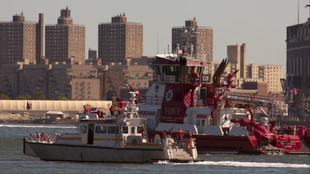 multiple fdny boats grouped up on the east river in new york city. - fire department of the city of new york stock-videos und b-roll-filmmaterial