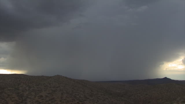 Multiple Forked Cloud to Ground lightning bolt trough very heavy rain shower over mountains. With distant rumble of thunder at end of clip.  Sonoran Desert near Tucson Arizona, USA.