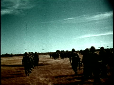 multiple helicopters in flight / two army helicopters pass over ground troops - guerra del vietnam video stock e b–roll