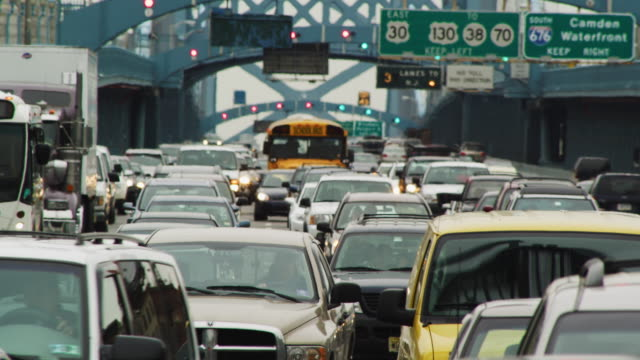 vídeos de stock e filmes b-roll de multiple lanes of early morning commuter traffic and congestion including a yellow school bus  move toward camera crossing the george washington bridge. - filadélfia pensilvânia