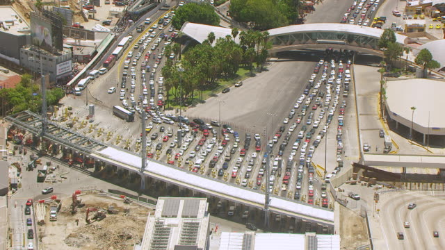 WS AERIAL POV Multiple lanes of stopped traffic in Tijuana Mexico at international border crossing with San Diego / San Diego, California, United States