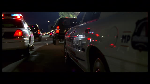 DS Multiple law enforcement vehicles driving together with lights flashing / Washington, D.C., United States