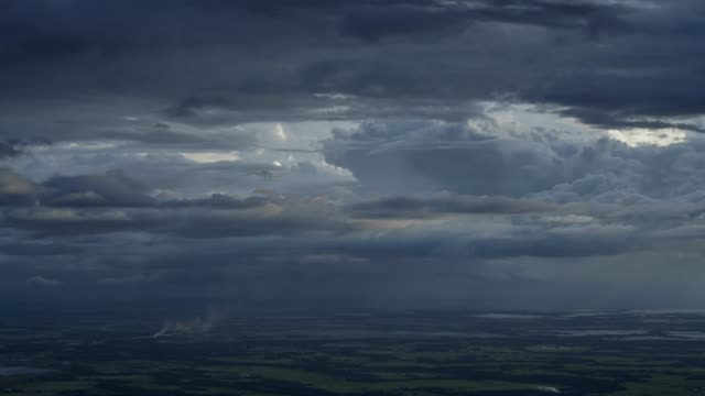 multiple layers dramatic of clouds moving horizantally over plains with passing rain at distant. - ネイチャーズウィンドウ点の映像素材/bロール