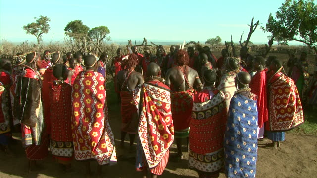 multiple - maasai men take turns jumping up and down in africa as a crowd claps around them / kenya - masai stock videos and b-roll footage