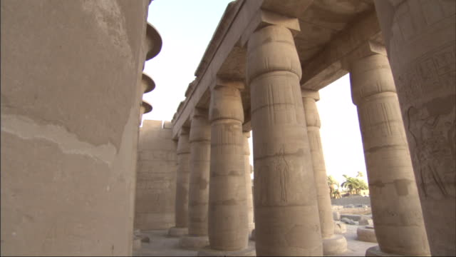 Multiple, pan-left push-in tracking-left - The columns of a ancient Egyptian building contain drawings and hieroglyphics